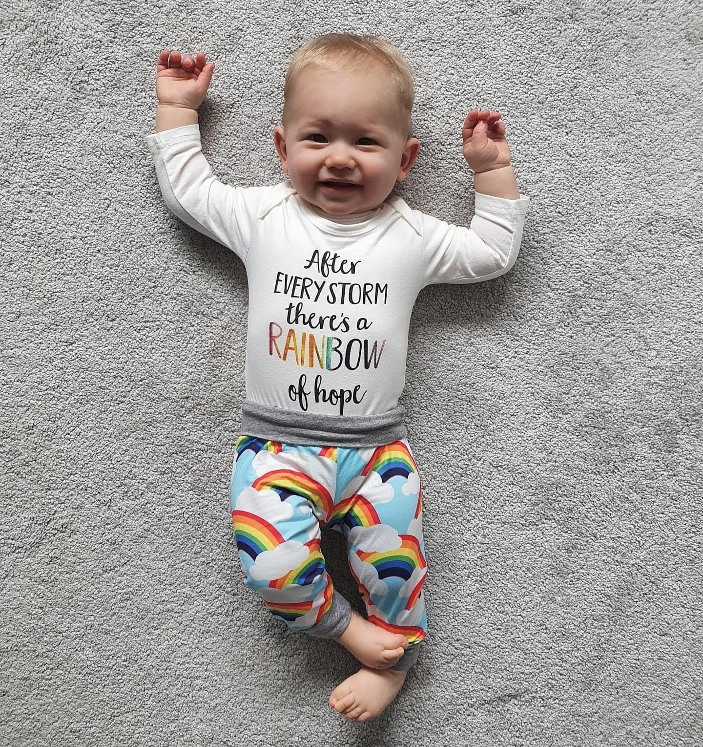 baby in rainbow pants